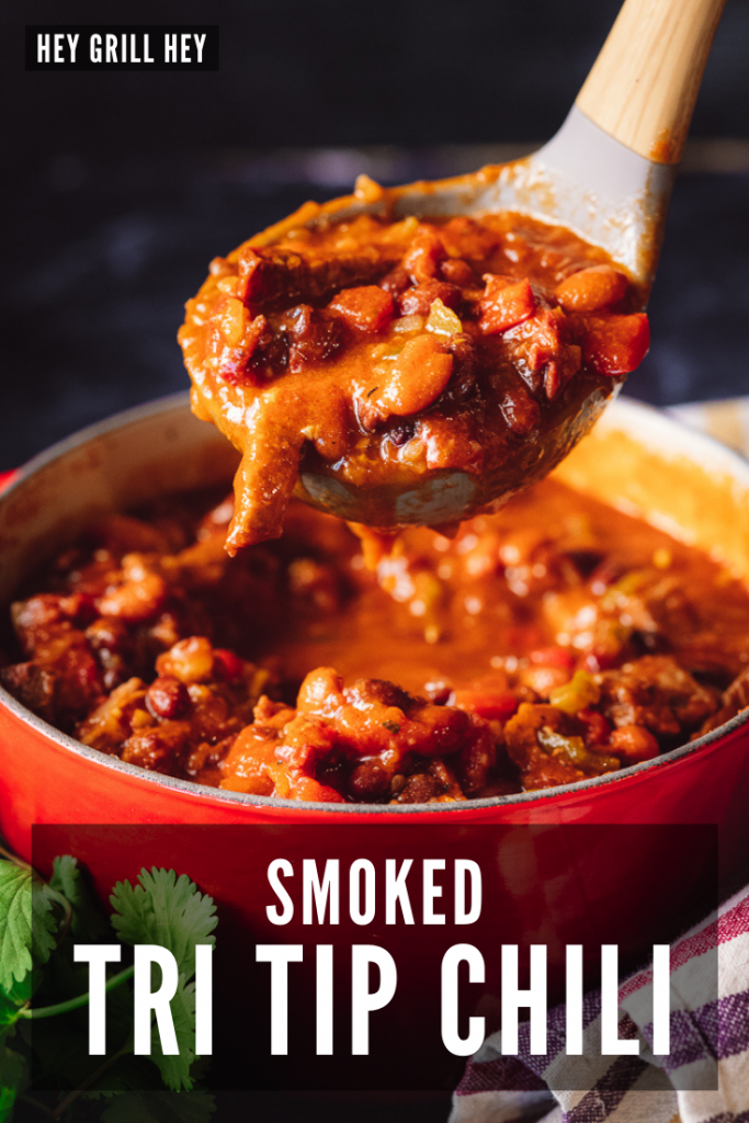 Wooden ladle taking a scoop out of a red dutch oven full of smoked tri tip chili. Text overlay reads: Smoked Tri Tip Chili.