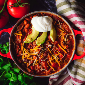 Overhead shot of smoked tri tip chili in a red dutch oven topped with shredded cheese, sliced avocado and a dollop of sour cream.