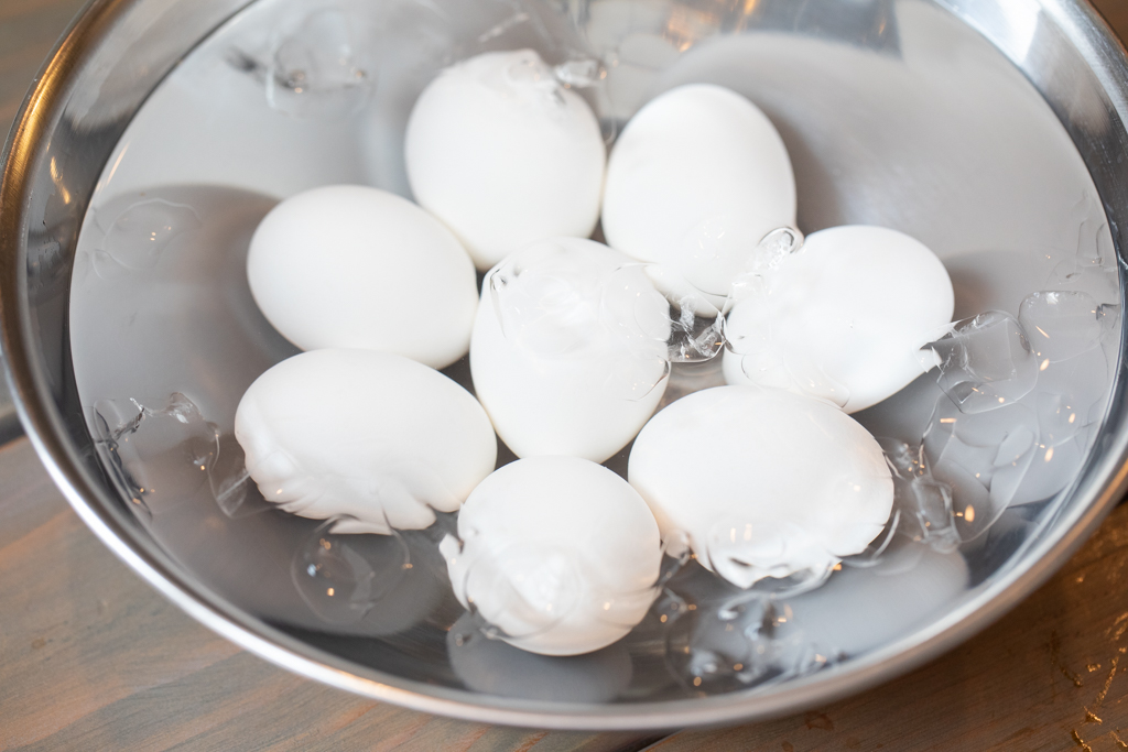 Eight eggs in a metal bowl full of water.