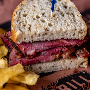 Homemade pastrami sandwich on peach Hey Grill Hey butcher paper next to potato chips.