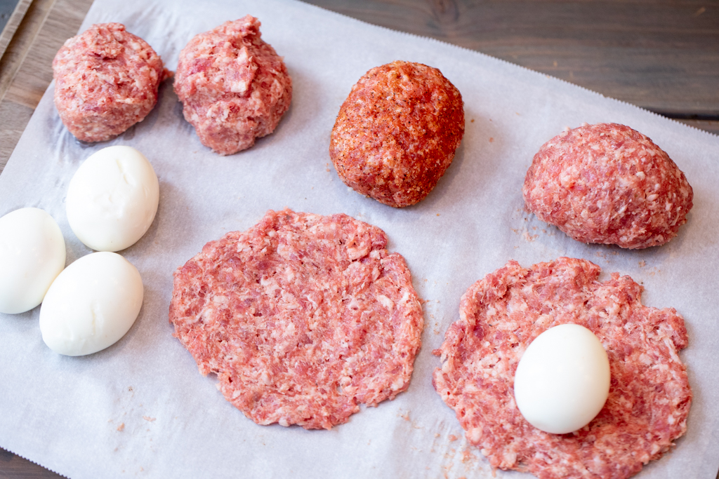 Breakfast sausage on parchment paper in various stages of being wrapped around eggs.