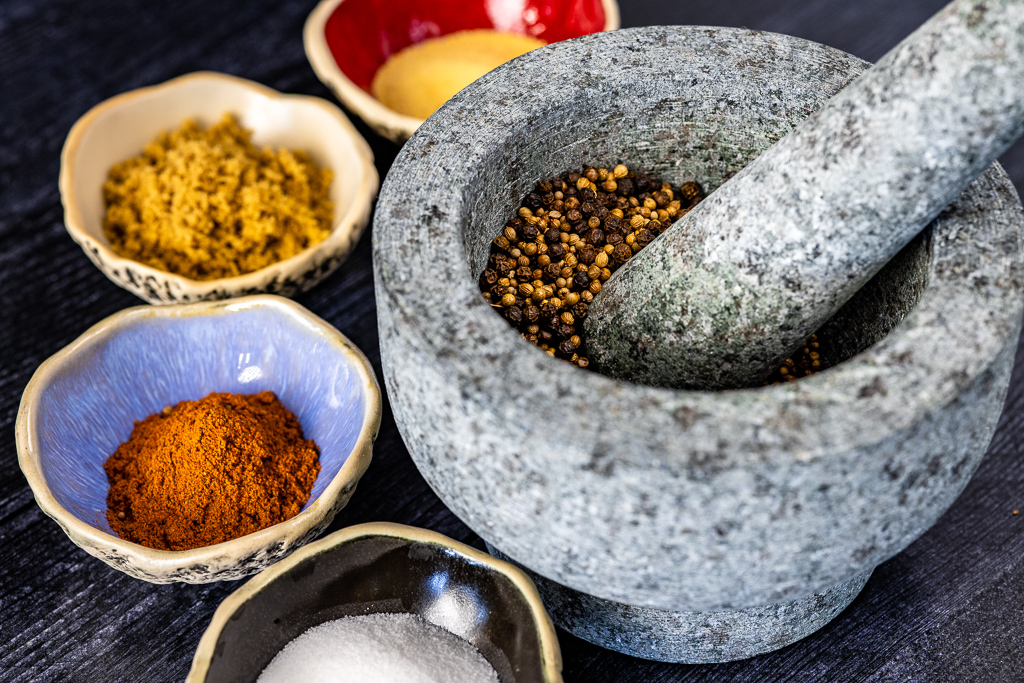 Ingredients for pastrami seasoning in small bowls with various seeds in a mortal and pestle.