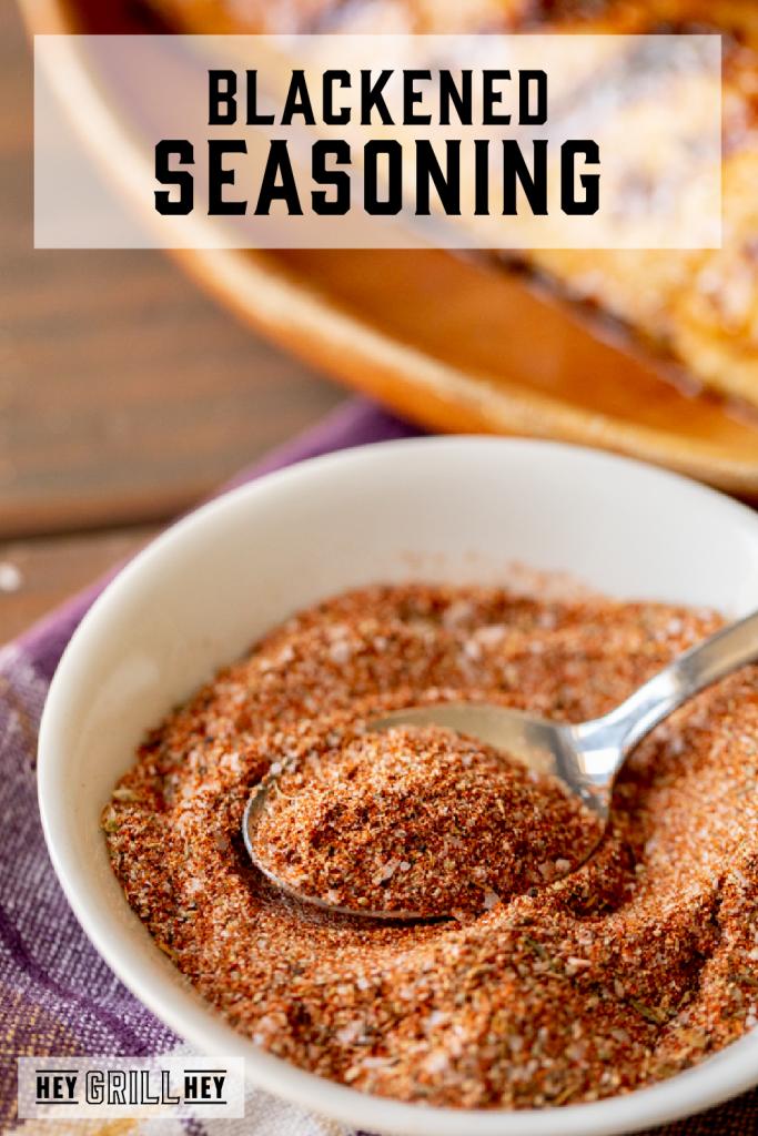 Blackened seasoning on a metal spoon over a white bowl with text overlay - Blackened Seasoning.