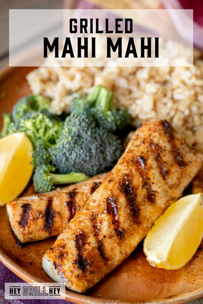 Two grilled mahi mahi filets on a plate surrounded by broccoli, rice, and lemon wedges with text overlay - Grilled Mahi Mahi.