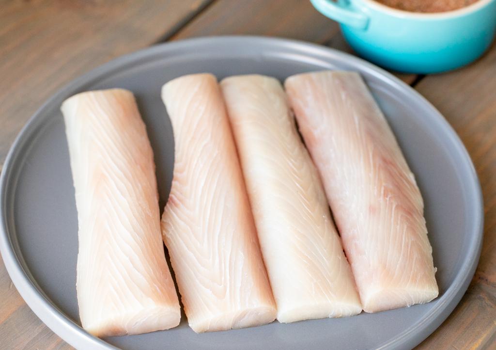 Four uncooked mahi mahi filets on a metal baking dish.