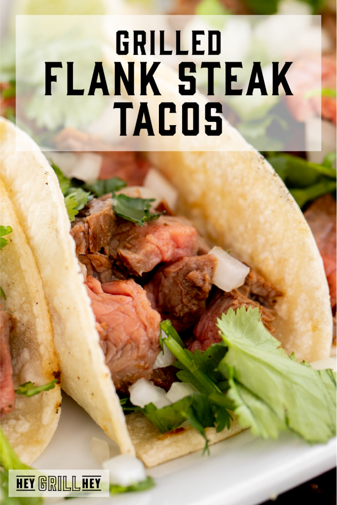 Flank steak taco on a white plate with text overlay - Grilled Flank Tacos
