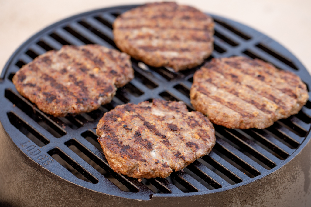 Four grilled bison burgers on the grill grates of a grill.