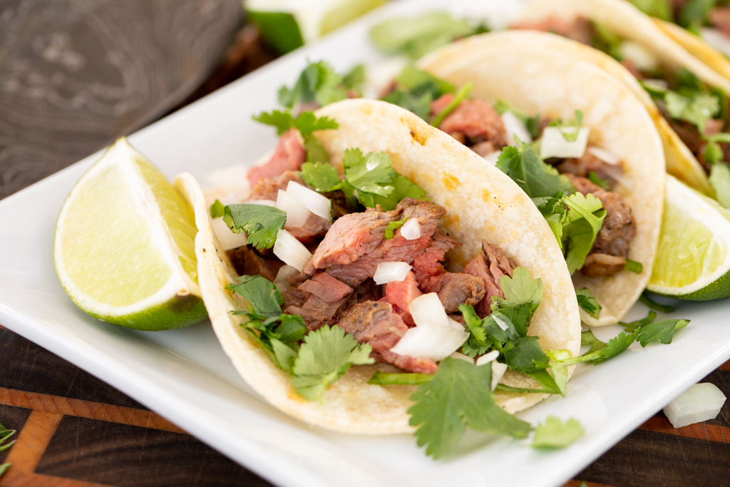 Two flank steak tacos topped with sliced onions and fresh cilantro on a white plate.