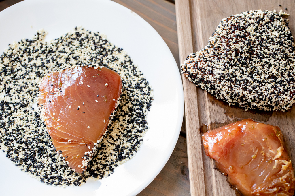Marinated tuna steak on a plate of sesame seeds.