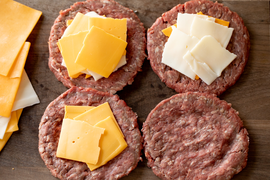 Formed burger patties covered with slices of cheese.